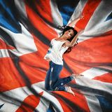 Girl jumping and flying. On the background of the British flag stock photo