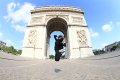 Girl jumping in front of Arc de Triomphe. Girl - young woman jumping in front of Arc de Triomphe in Paris (France Royalty Free Stock Images