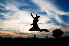 Girl jumping in front of beautiful sunset Royalty Free Stock Images