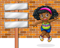 A girl jumping in front of the stonewall beside the empty signbo Royalty Free Stock Photography