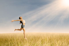 Girl jumping in golden wheat Royalty Free Stock Image