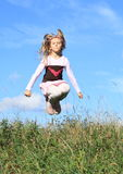 Girl jumping in grass Stock Images