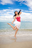 Girl jumping happily. With one hand holding hair by the beach and blue sky Stock Photos