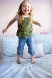 Girl Jumping on her bed Stock Photos