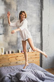 Girl jumping on her bed in shirt. Happy young woman jump on the bed at home Royalty Free Stock Photo