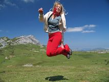 Girl jumping high. Beautiful girl jumping high in the mountain Royalty Free Stock Photo