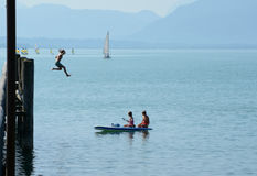 Girl jumping from high pier to water and two other on kayak Royalty Free Stock Photography