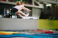 Girl jumping high in striped tights on trampoline. royalty free stock image