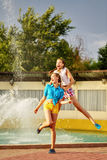 Girl jumping holding the shoulders of her best friend. Girl jumping, holding the shoulders of her best friend, near the fountain in the summer park. Girls Stock Images
