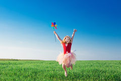 Girl jumping and  holding a toy flower Royalty Free Stock Photos