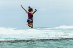 Girl Jumping Holidays Beach Tidal Pool Ocean. Teenager girl holidays happy jumping on beach tidal pool wall with overcast ocean waves on horizon Royalty Free Stock Image