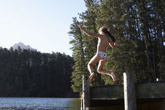 Girl Jumping From Jetty Into Lake Royalty Free Stock Photography