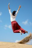 Girl jumping for joy. From the dunes in Gran Canaria Royalty Free Stock Photography