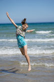 Girl jumping for joy. Young, happy girl jumping in the beach water Royalty Free Stock Photo