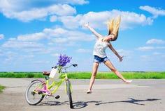 Girl jumping joyfully next to her bike Stock Images