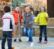 Girl jumping while jump rope game with friends. Smiling positive girl jumping while jump rope game with friends outdoor Stock Photography