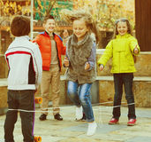 Girl jumping while jump rope game with friends. Smiling positive girl jumping while jump rope game with friends outdoor Stock Photos