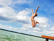 Girl jumping into lake. Royalty Free Stock Photos
