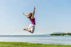 Girl jumping on the lake Royalty Free Stock Images