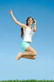 Girl jumping with mobile phone Stock Images