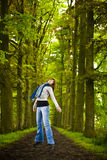 Girl jumping in the nature. Woman jumping in beautiful road surrounded by big trees Royalty Free Stock Image