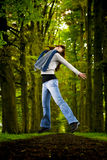 Girl jumping in the nature. Woman jumping in beautiful road surrounded by big trees Royalty Free Stock Photos