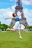 Girl jumping near the Eiffel Tower in Paris Royalty Free Stock Photo