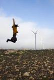 Girl jumping near to some mills wind. In Zaragoza, Spain Stock Photo