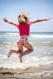 Girl jumping in the ocean Stock Image