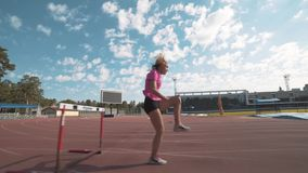 Girl jumping over barriers during training. Jumping over barriers. Running with obstacles stock footage
