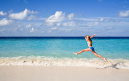 Girl jumping over the beach and waves Royalty Free Stock Images