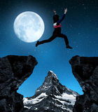 Girl jumping over the gap in night. Royalty Free Stock Photo