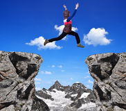 Girl jumping over the gap. Swiss Alps royalty free stock photos