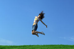 Girl jumping over grass. Girl jumping over a green grass Royalty Free Stock Photo
