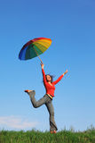 Girl jumping over grass with colorful umbrella Royalty Free Stock Photos
