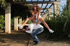 Girl jumping over a man Royalty Free Stock Photos
