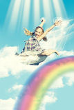 Girl jumping over rainbow royalty free stock photo