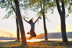 Girl jumping over sunset Stock Photo