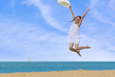 Girl jumping over the water at the beach Stock Images