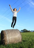 Girl jumping from package of hay Stock Photography