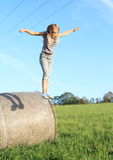 Girl jumping from package of hay Stock Photo