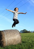 Girl jumping from package of hay Royalty Free Stock Images