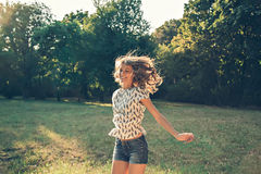 Girl jumping in a park. Happy girl jumping in a park Royalty Free Stock Photography
