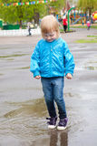 A girl is jumping in the puddle Royalty Free Stock Images