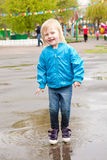 A girl is jumping in the puddle Stock Photography