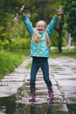 Girl jumping at the puddle Stock Photo