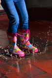 Girl jumping in the puddle Stock Photo
