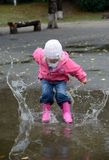 Girl jumping in puddles Stock Images