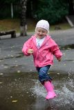 Girl jumping in puddles stock image