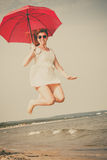 Girl jumping with red umbrella on beach. Stock Image